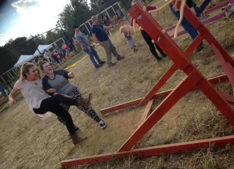 Our older girls laughing seconds after launching a pumpkin through the air using a giant slingshot.