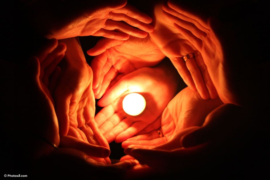 many hnds surrounding a candle